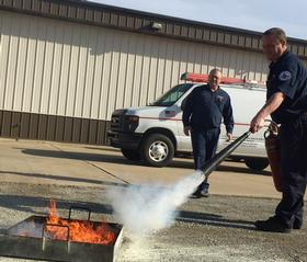 Picture of professional demonstrating how a fire extinguisher works